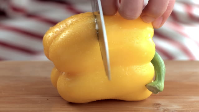 Human hands slicing yellow paprika with knife