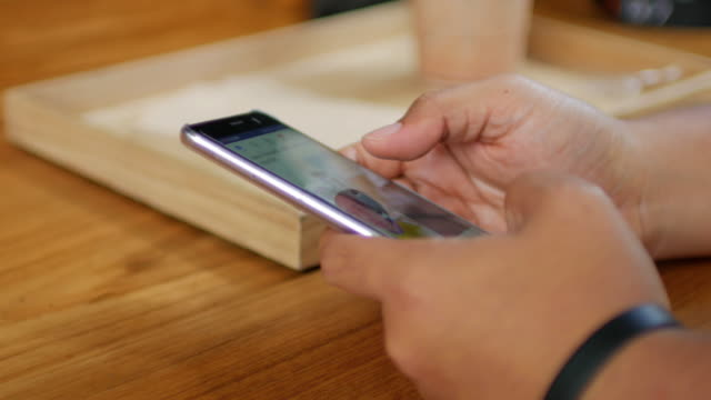 Human hands touching smartphone on wooden table at coffee cafe