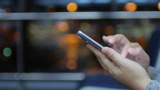 Menselijke handen aanraken Smartphone met Bokeh cirkel lichte achtergrond bij Airport terminal