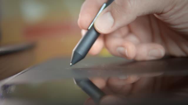 vídeos de stock, filmes e b-roll de mãos humanas usando tablet gráfico, close-up - caneta