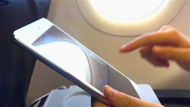 human hands using tablet on airplane