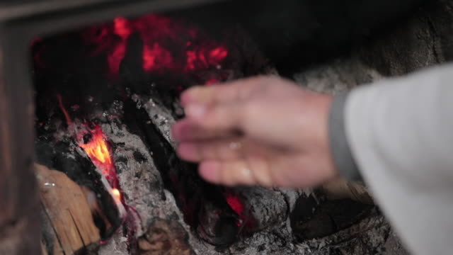 human hands watering over burning firewood in the furnace - ash stock videos & royalty-free footage