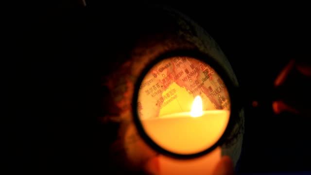 Mänskliga tittar genom förstoringsglas på globe med ljus på natten