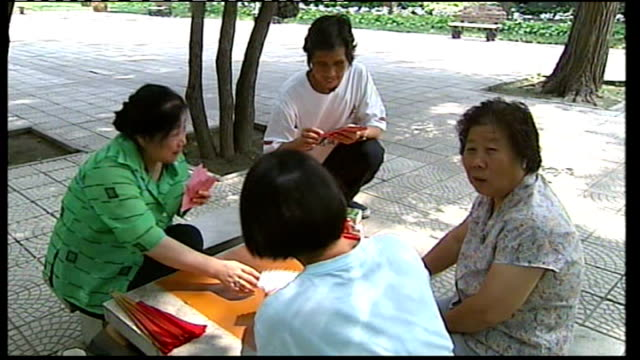 Human rights questions raised over applications to protest Group of Chinese women sat in park playing cards Stream shaded by trees Bilingual park...