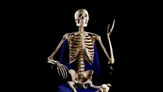 Human skeleton sitting at chair and talking
