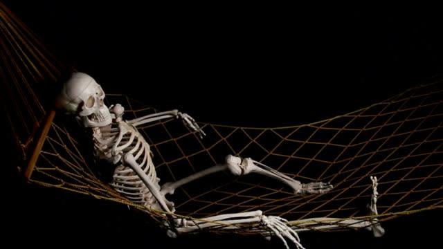 human skeleton swingig on hammock - human skeleton stock videos & royalty-free footage
