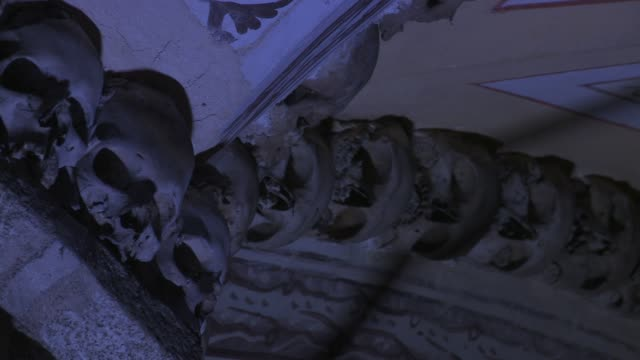 human skulls decorate the ceiling moldings in the chapel of bones in evora, portugal. - évora district stock videos & royalty-free footage
