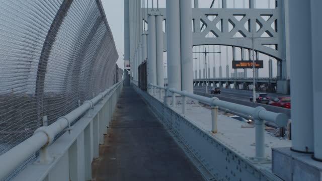 vídeos y material grabado en eventos de stock de pov human walking looking up fence dusk bridge nyc skyline - cámara en mano