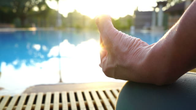 human workout yoga and meditating at poolside  , sun flare , zoom out - deltoid stock videos and b-roll footage