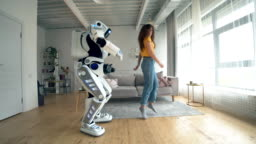 Human-like robot and a woman are dancing and jumping