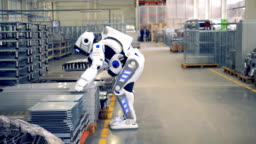 A human-like robot is putting a piece of fitting and walking away in a factory warehouse.