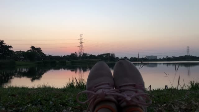 pov , human's feet sitting at lakeside with sunset scene - only teenage girls stock videos & royalty-free footage