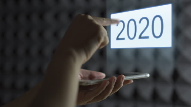 human's hand holding smart phone screen to show hologram and swipes to change year 2019 to new year 2020. year change hologram. - 2020 business stock videos and b-roll footage