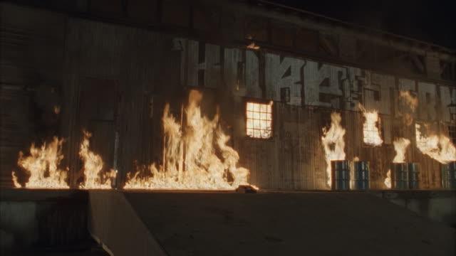 stockvideo's en b-roll-footage met ms hummer crashing through wall of burning warehouse at night - hummer