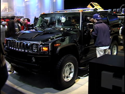 ws hummer h2 logo sign pan to ws black hummer h2 with people all around / ws hummer front end / ms rear end interior with folded up hummer mountain... - hummer stock-videos und b-roll-filmmaterial