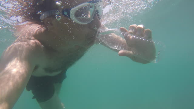 humor: funny scene in which a man drinks water from a bottle while diving in the sea. - 使い捨て製品点の映像素材/bロール