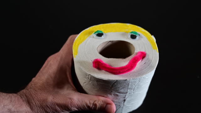 humor. funny toilet paper with human face.  man's hand takes it. - unfall und katastrophe stock-videos und b-roll-filmmaterial
