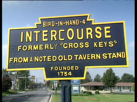 humorous road sign of amish town reading 'bird in hand 4 - intercourse - founded 1754' traffic passes by and moves along background intercourse - amish stock videos & royalty-free footage