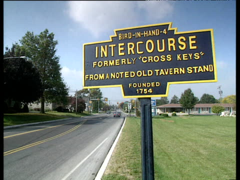 humorous road sign of an amish town reading 'bird in hand 4 - intercourse founded 1754' traffic passing intercourse - amish stock videos & royalty-free footage