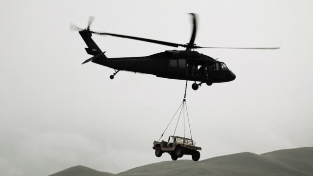 humvee being hauled by black hawk helicopter from field.  - special forces stock videos & royalty-free footage