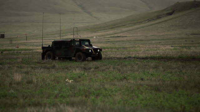 Humvee drives in field