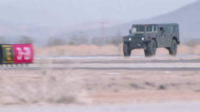 a humvee speeds down an airport runway. - humvee stock videos & royalty-free footage