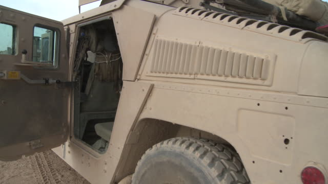 A Humvee, with an open door, displays armor enhancements and additional equipment.
