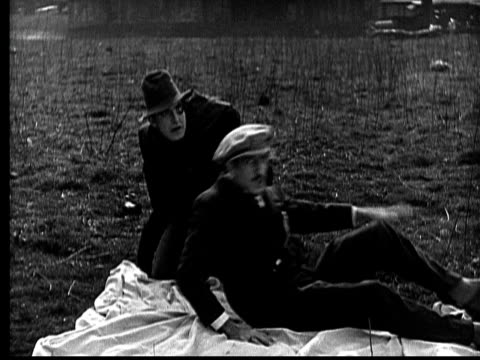 ms, b&w, hunchback swapping places with man lying on sheet in field, 1910's  - bedclothes stock videos & royalty-free footage