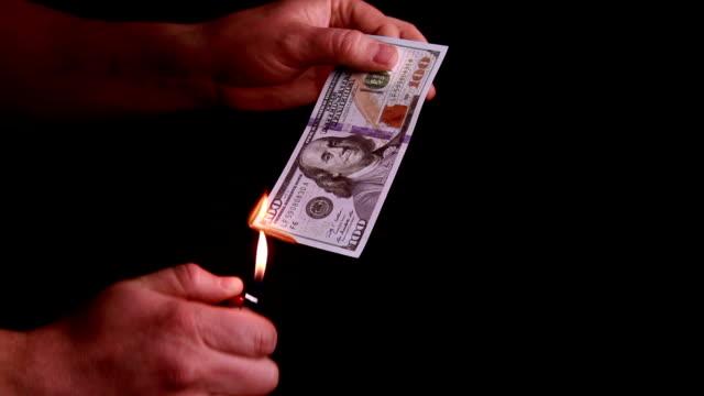 Hundred dollars bill burning in hand