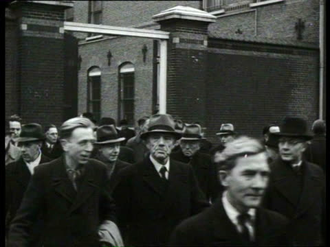 stockvideo's en b-roll-footage met hundred ex-hostages from wwii gather at the haarlem prison in memory of ten comrades shot down by the germans, in the town hall a panel with the name... - 1946