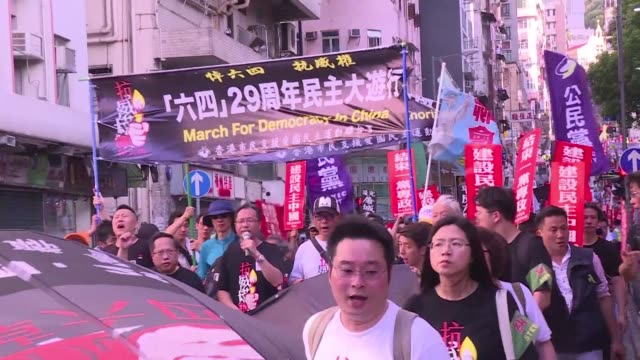 stockvideo's en b-roll-footage met hundreds march through hong kong ahead of the 29th anniversary of china's crackdown on democracy protesters in beijing's tiananmen square - plein van de hemelse vrede