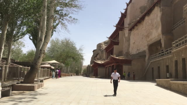 hundreds of caves with buddhist statues and wall paintings were cut into a cliff of two kilometers long the mogao caves also known as the thousand... - gesellschaftsgeschichte stock-videos und b-roll-filmmaterial