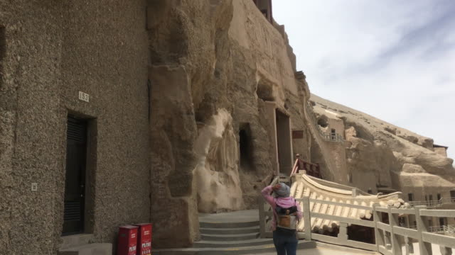 hundreds of caves with buddhist statues and wall paintings were cut into a cliff of two kilometers long the mogao caves also known as the thousand... - storia sociale video stock e b–roll