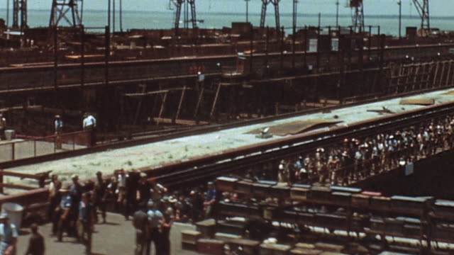 hundreds of civilian workers leaving the shipyard after work with gantry cranes standing idle / newport news virginia united states - dockarbeiter stock-videos und b-roll-filmmaterial
