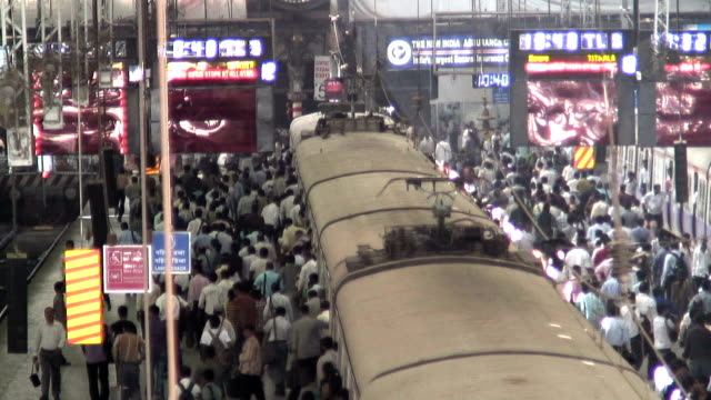hundreds of commuters disembark a train at the victoria terminus in mumbai, india. - india video stock e b–roll