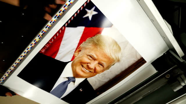 Hundred's of copies of the official photograph of President Donald Trump are stacked and trimmed at the US Government Publishing Office December 4...