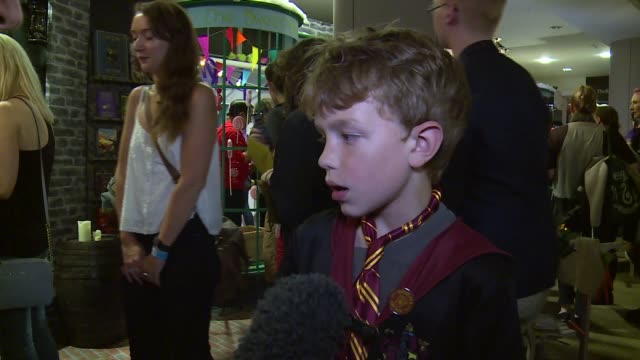 hundreds of fans queue for 'harry potter and the cursed child' screenplay harry potter quiz / props on display and quidditch match in progress / vox... - harry potter stock videos & royalty-free footage