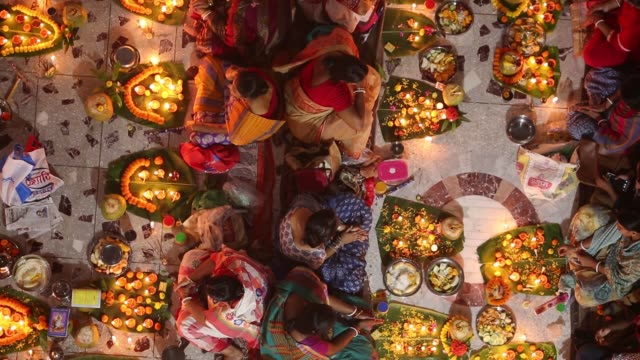 vídeos y material grabado en eventos de stock de hundreds of hindu devotees sits with prodip and prays to god in front of shri shri lokanath brahmachari ashram temple during the kartik brati or... - hinduismo