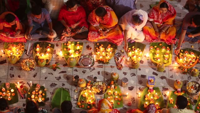 Hundreds of Hindu devotees sits with Prodip and prays to God in front of Shri Shri Lokanath Brahmachari Ashram temple during the Kartik Brati or...