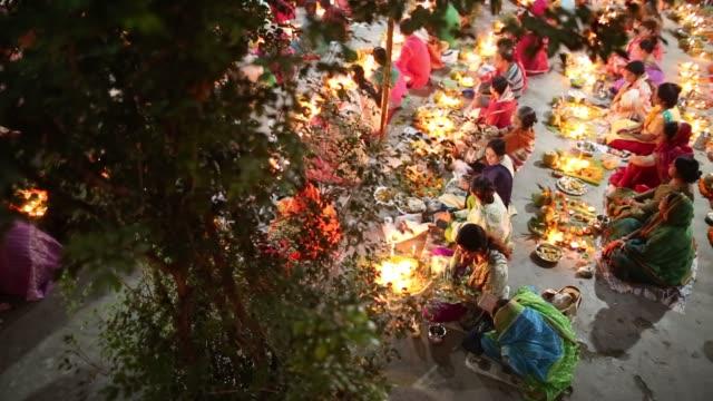 Hundreds of Hindu devotees sits with Prodip and prays to God in front of Shri Shri Lokanath Brahmachari Ashram temple during the Kartik Brati or...