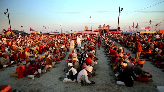 Hundreds of holymen sit in lines, back to back, at the Kumbh Mela, while food is handed out to them, lit by late afternoon sun. India.