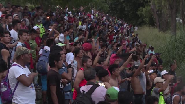 Hundreds of Honduran migrants who made it into Mexican territory sing their country's national anthem on the shore of the Suchiate river while...
