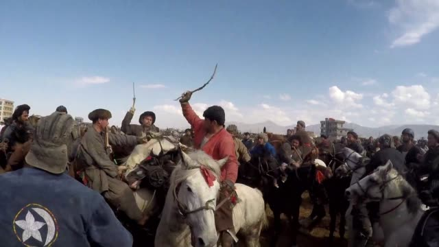 vídeos de stock e filmes b-roll de hundreds of horsemen crack their whips as they battle for the headless carcass of a calf carrying on the eight centuries old tradition of buzkashi... - decapitado