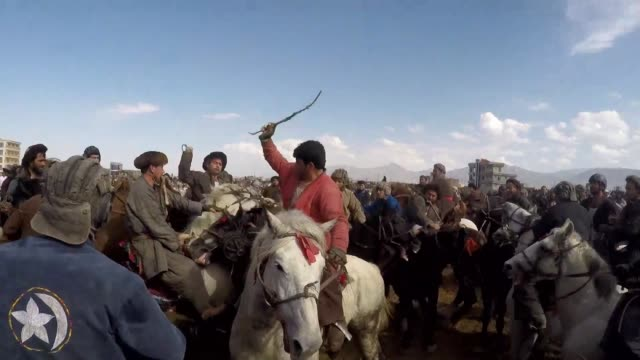 vídeos y material grabado en eventos de stock de hundreds of horsemen crack their whips as they battle for the headless carcass of a calf carrying on the eight centuries old tradition of buzkashi... - decapitado
