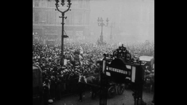 Hundreds of jubilant English people celebrate armistice in the streets of London / Various shots of a heavily congested London street with hundreds...