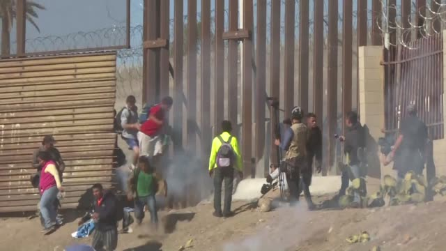 hundreds of migrants attempt to breach the us mexico border fence but are stopped by us border officers who began firing tear gas according to an afp... - tear gas stock videos & royalty-free footage