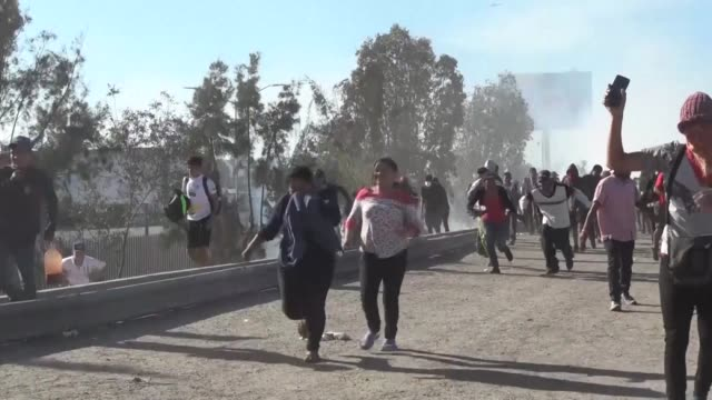 hundreds of migrants face off with riot police when they attempt to cross the us mexico border causing the us to close the san ysidro border crossing... - national border stock videos & royalty-free footage