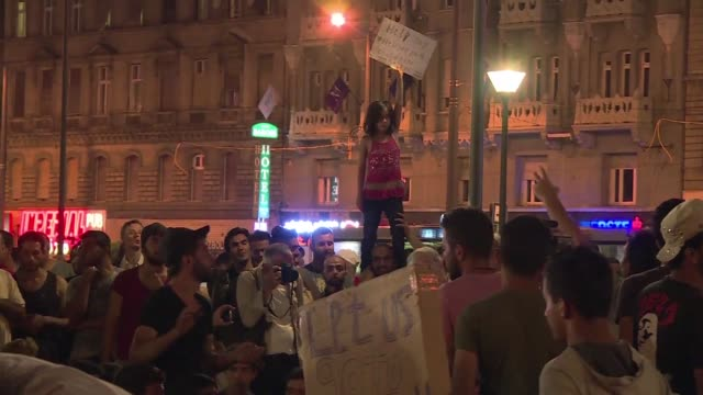 vídeos de stock, filmes e b-roll de hundreds of migrants gathered outside of keleti train station in budapest on monday night after hungarian police blocked them from boarding trains to... - cultura do leste europeu