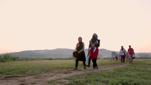 Hundreds of mostly Syrian families walk the final few kilometers through fields towards the Macedonian border to have their papers processed before...