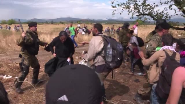 stockvideo's en b-roll-footage met hundreds of mostly syrian refugees forced their way over the macedonian border saturday as police hurled stun grenades in a failed bid to stop them... - athene griekenland